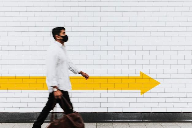 Homme passant devant un mur de briques blanches