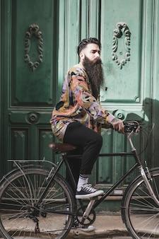 Homme passant sur la porte ancienne de vélo vert au soleil