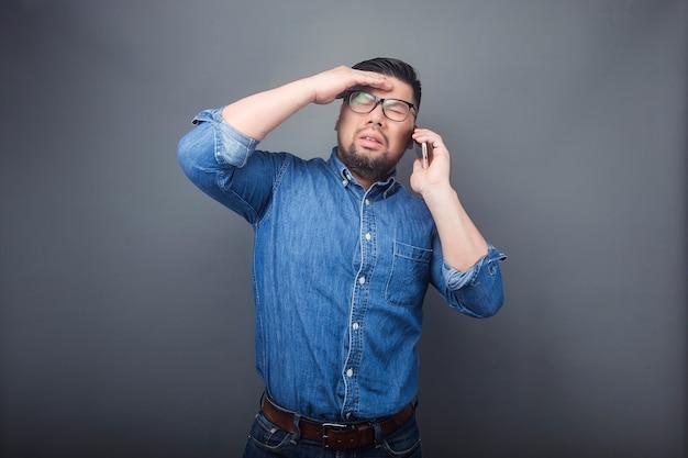 Un homme passe un appel téléphonique avec une expression surprise.