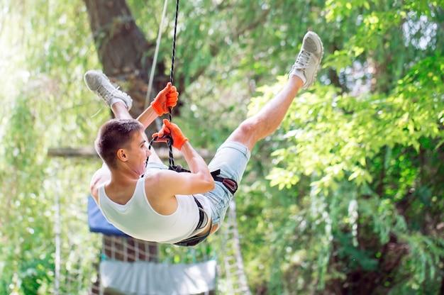 L'homme passe ses loisirs dans un parcours de cordes. homme engagé dans le parc de corde.