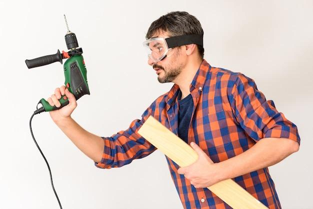 L'homme passionné de bricolage tient une perceuse. fond blanc. chemise unie.