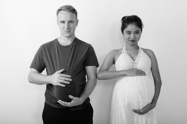 Homme avec pastèque comme estomac et femme asiatique enceinte ensemble en tant que couple marié multiethnique en noir et blanc