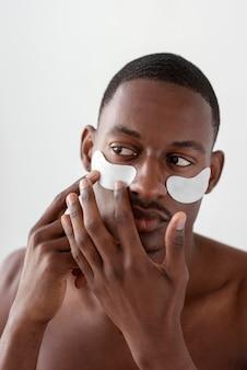 Homme avec des patchs oculaires se bouchent