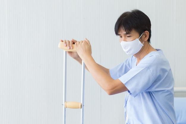 Homme patient asiatique qui porte un masque facial et tient la béquille marchant à cause de sa jambe cassée