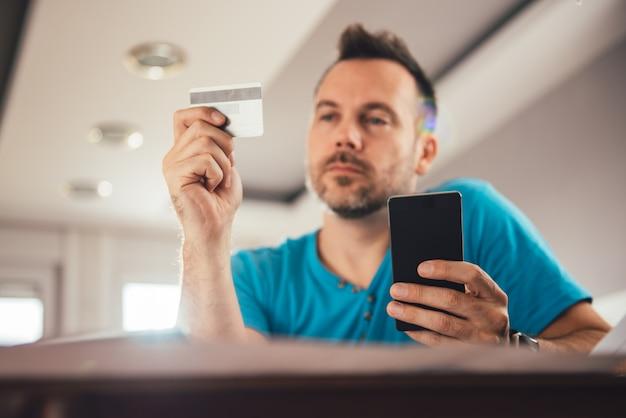 Homme payant avec carte de crédit sur smartphone