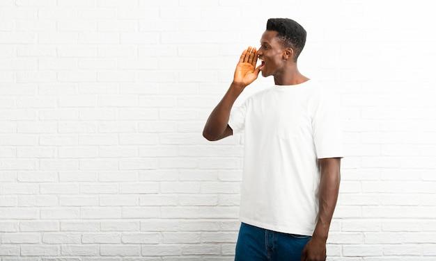 Homme à la peau foncée criant avec la bouche grande ouverte sur le côté et annonçant quelque chose