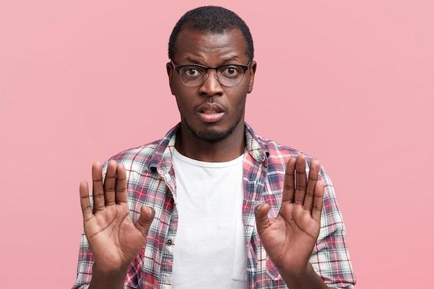 Un homme à la peau foncée portant des lunettes refuse de faire quelque chose, garde les paumes au premier plan, refuse ou refuse d'aller quelque part, porte des lunettes et une chemise à carreaux, isolé sur rose