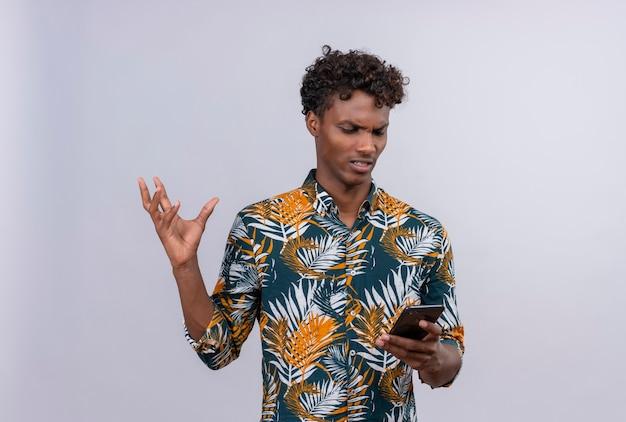 Homme à la peau sombre en colère et nerveux en chemise imprimée de feuilles à la recherche de téléphone mobile et de lever la main