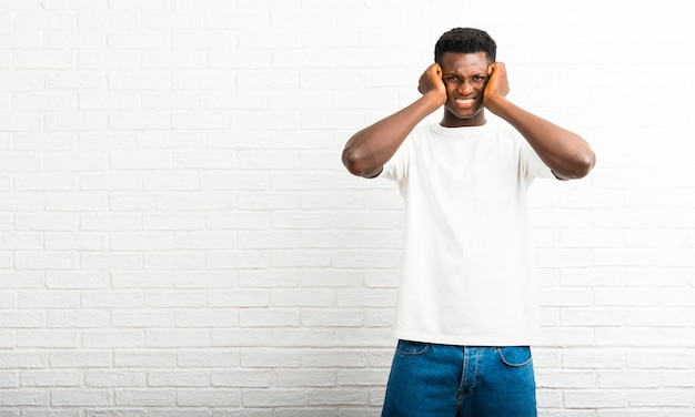 Homme à la peau sombre couvrant les deux oreilles avec les mains. expression frustrée