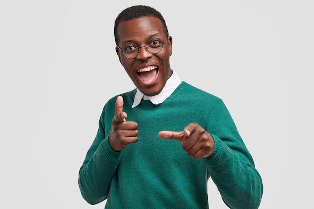 Un homme à la peau sombre et ravi de joie montre du doigt avec les deux index, des indices sur quelque chose, porte un pull vert décontracté, sourit largement