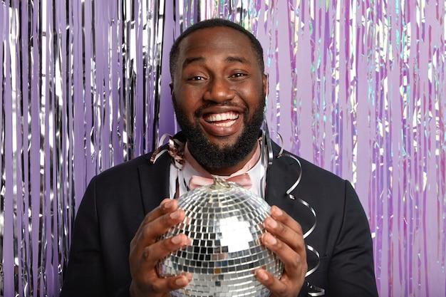 Un homme à la peau sombre ravi tient une boule disco, célèbre quelque chose à la fête, porte un costume élégant, regarde avec plaisir, se tient au-dessus d'un mur violet avec un rideau de guirlandes, a un large sourire, montre des dents blanches