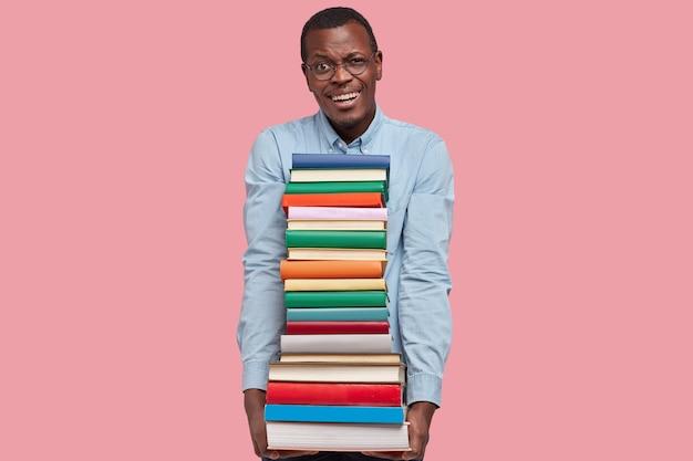 Homme à la peau sombre et satisfait positif avec une expression heureuse, montre des dents blanches, tient des manuels à deux mains, porte une chemise formelle