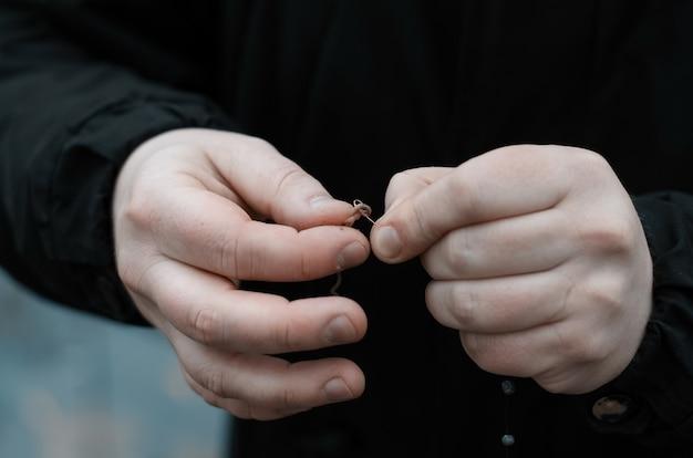 Homme pêchant dans un lac sauvage. mains mâles appâtant un ver sur un crochet, gros plan. pêche d'automne par temps froid.