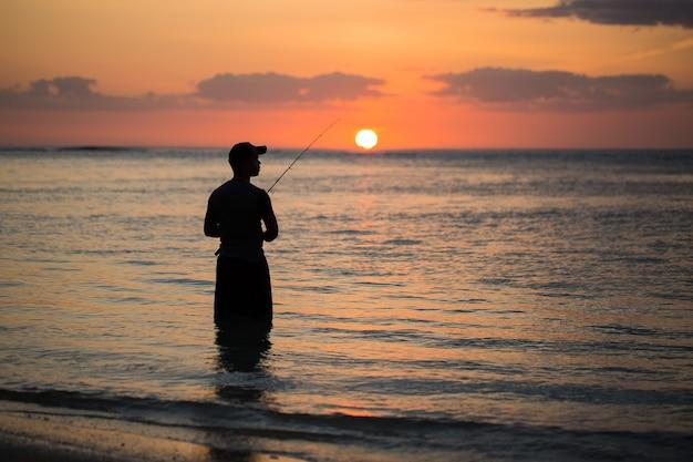 Homme de pêche dans l'océan indien avec la plage au coucher du soleil
