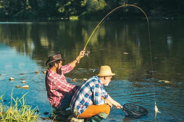 Homme pêcheur attrape un poisson. la pêche à la mouche est la méthode la plus connue pour attraper l'ombre de la truite