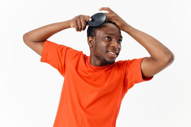 Homme peignant les cheveux d'apparence africaine soins de la tête fond clair