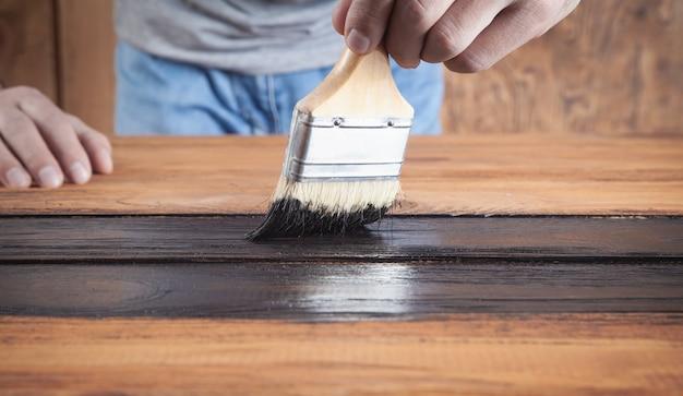 Homme peignant du bois avec un pinceau.