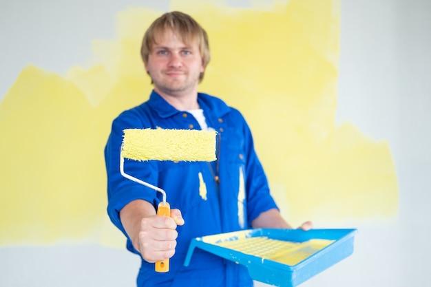 Homme peignant un mur de couleur jaune avec un concept de réparation et de redécoration de rénovation de rouleaux sélectif f...