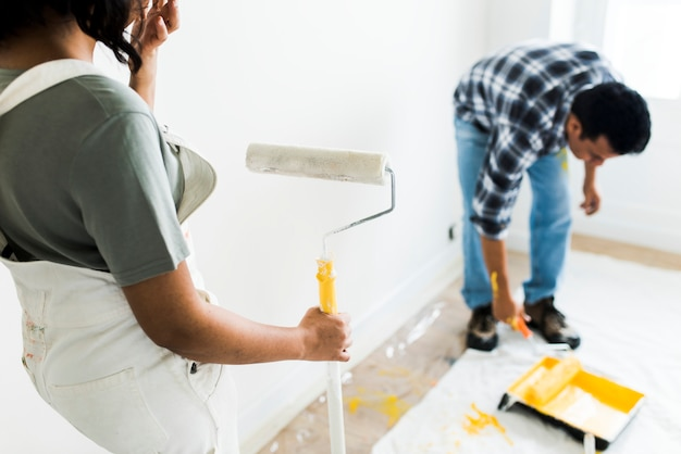 Homme peignant les murs jaune