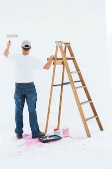 Homme peignant par échelle sur fond blanc