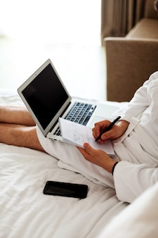 Un homme en peignoir est allongé sur un lit avec un ordinateur aux pieds. indépendant, travail à domicile. pas de visage. un homme dans un hôtel, travaillant dans une chambre devant un ordinateur. verticale