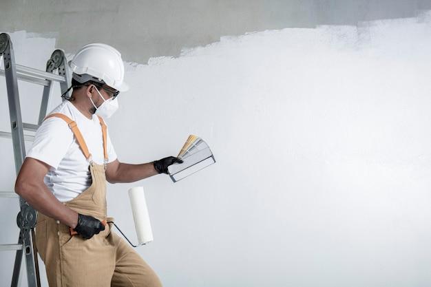Un homme peint un mur blanc avec un rouleau. réparation de l'intérieur. jeune décorateur masculin peignant un mur dans la pièce vide, constructeur de concept ou peintre en casque avec rouleau à peinture sur la pièce vide.