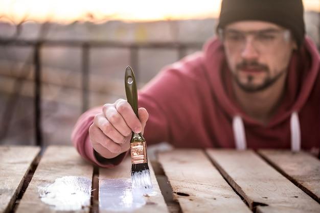 L'homme peint avec de la peinture blanche sur des planches de bois