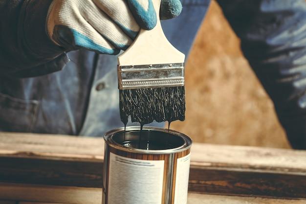 Un homme peint un produit en bois fait à la main avec de la peinture dans un atelier