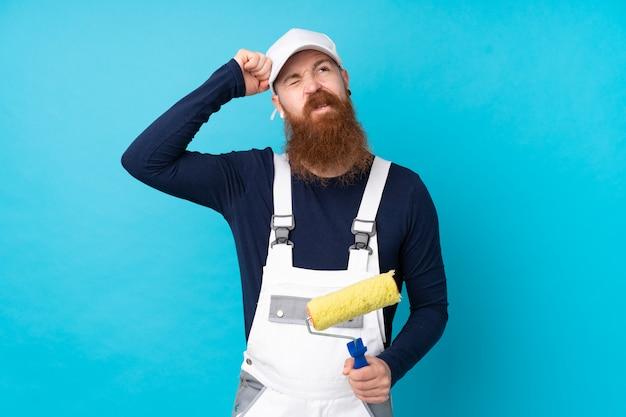 Homme peintre avec longue barbe sur bleu isolé ayant des doutes et avec une expression de visage confuse
