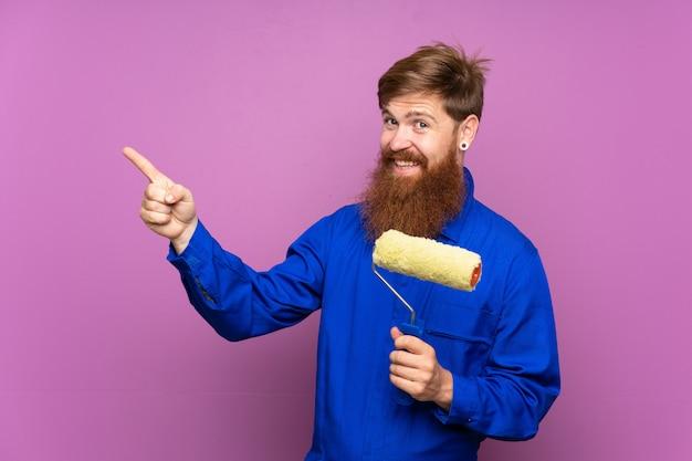 Homme peintre avec une longue barbe sur fond violet isolé, pointant le doigt sur le côté
