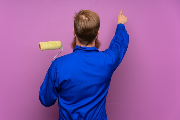 Homme peintre avec une longue barbe sur fond violet isolé pointant vers l'arrière avec l'index