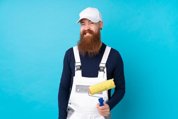 Homme peintre avec longue barbe sur mur bleu ayant des doutes et avec une expression de visage confuse