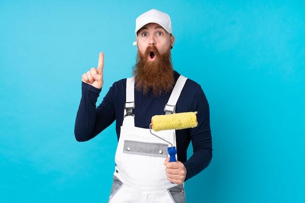 Homme peintre avec longue barbe sur mur bleu avec expression faciale surprise