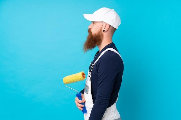 Homme peintre avec longue barbe sur mur bleu isolé à côté