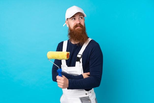 Homme peintre avec longue barbe sur mur bleu isolé en riant