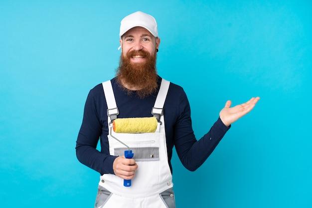 Homme peintre avec longue barbe sur mur bleu tenant un espace vide imaginaire sur la paume