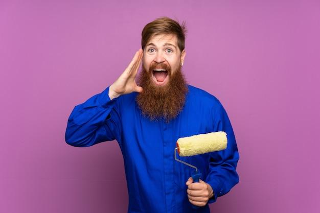 Homme peintre avec une longue barbe sur un mur violet isolé criant avec la bouche grande ouverte