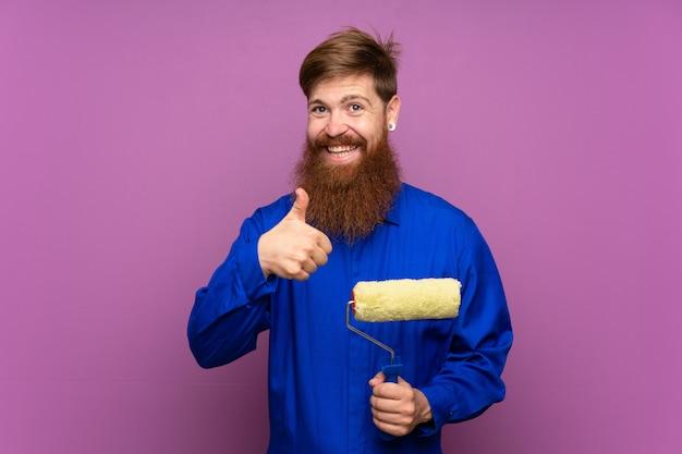 Homme peintre avec une longue barbe sur un mur violet isolé donnant un geste du pouce levé