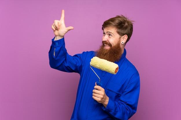 Homme peintre avec une longue barbe sur un mur violet isolé pointant avec l'index une excellente idée