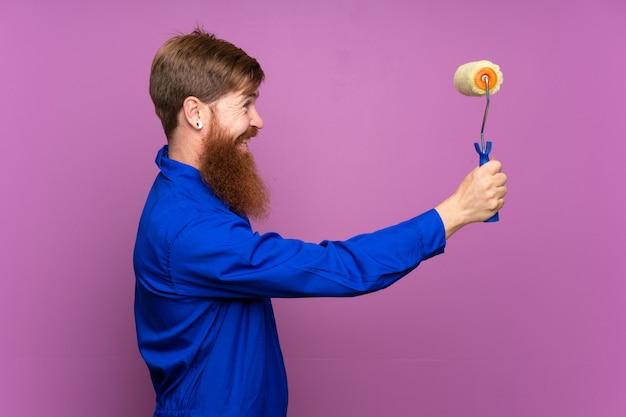 Homme peintre avec une longue barbe sur un mur violet isolé