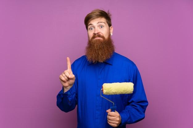 Homme peintre avec une longue barbe pointant avec l'index une excellente idée