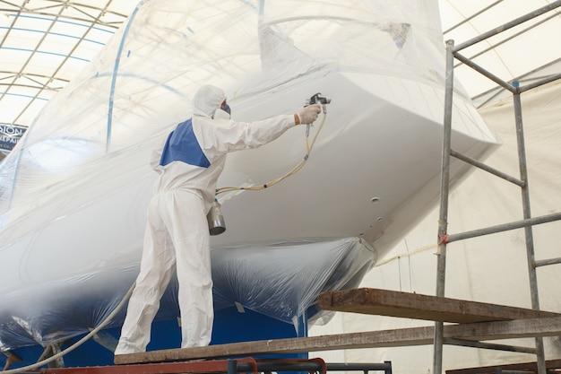 Homme avec une peinture blanche uniforme de pulvérisation sur le bateau