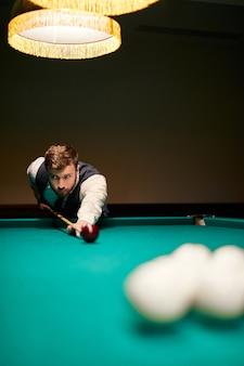 Homme penché sur la table tout en jouant au billard, il est concentré sur le jeu, ayant du temps libre