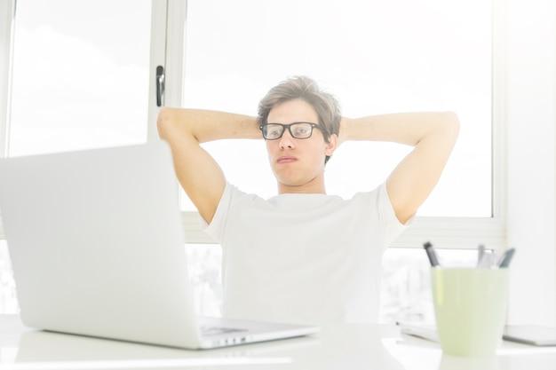 Homme, pencher dos, sien, chaise, regarder, ordinateur portable, table