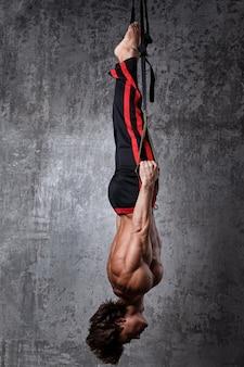 Homme pendant l'entraînement avec des sangles de suspension