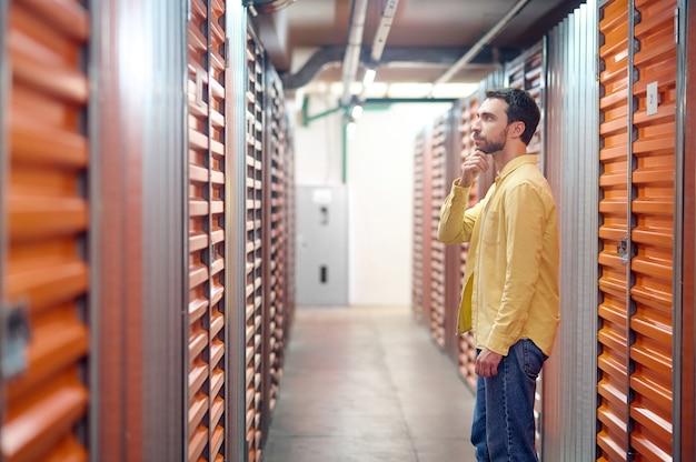 Homme pensant devant le conteneur au sous-sol