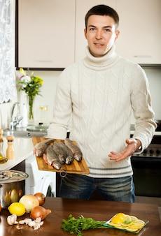 L'homme pense comment faire cuire le poisson