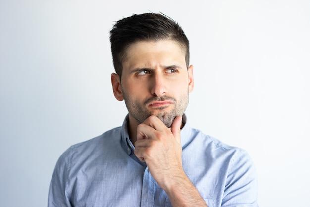 Homme pensif fronçant les sourcils dans la prise de décision