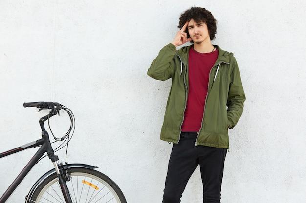 Un homme pensif garde le doigt sur les tempes, essaie de se souvenir de quelque chose, vêtu d'une veste verte, se tient près d'un vélo, isolé sur fond de béton blanc. concept de personnes, de jeunes et de transports