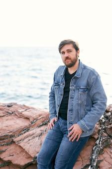 Homme pensif en jeans et veste en jean posant assis sur des pierres sur fond de mer